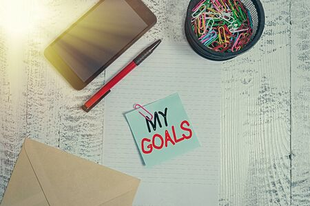 Handwriting text My Goals. Conceptual photo a future or desired result that a demonstrating commits to achieve Smartphone paper sheet clips holder pen envelope note wooden background Reklamní fotografie