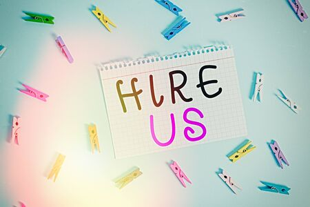 Writing note showing Hire Us. Business concept for Used by resources indicate employee that he is got job Colored clothespin rectangle shaped paper blue background Archivio Fotografico