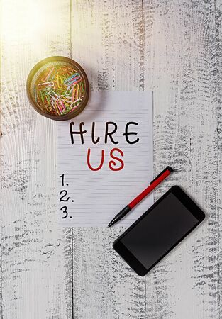 Text sign showing Hire Us. Business photo text Used by resources indicate employee that he is got job Smartphone paper sheet clips holder ballpoint wooden vintage background 写真素材