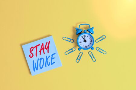 Conceptual hand writing showing Stay Woke. Concept meaning being aware of your surroundings and things going on Keep informed Metal vintage alarm clock clips notepad colored background Stock fotó