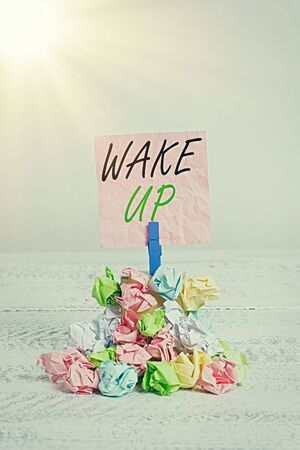 Conceptual hand writing showing Wake Up. Concept meaning an instance of a demonstrating waking up or being woken up Rise up Reminder pile colored crumpled paper clothespin wooden space