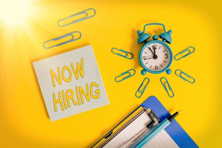 Handwriting text writing Now Hiring. Conceptual photo Workforce Wanted Employees Recruitment Today Job Opportunity Metal alarm clock clipboard clips ballpoint notepad colored background