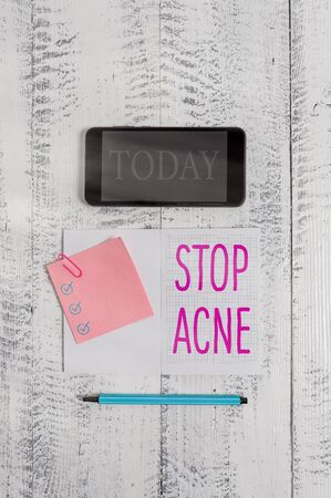 Conceptual hand writing showing Stop Acne. Concept meaning control the occurrence of inflamed sebaceous glands in the skin Squared notebook marker smartphone sticky note wooden background