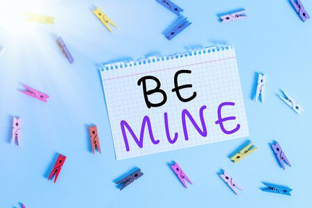 Writing note showing Be Mine. Business concept for like a demonstrating more than a friend and would like to date them Colored clothespin rectangle shaped paper blue background