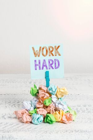 Text sign showing Work Hard. Business photo showcasing Laboring that puts effort into doing and completing tasks Reminder pile colored crumpled paper clothespin reminder white wooden space