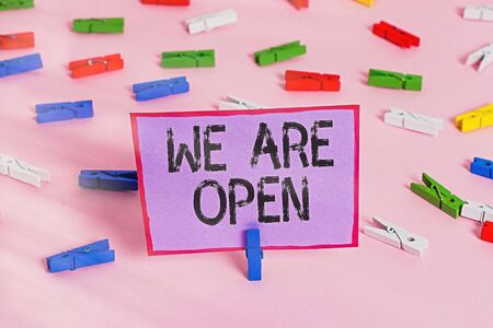 Writing note showing We Are Open. Business concept for no enclosing or confining barrier, accessible on all sides Colored clothespin papers empty reminder pink floor office pin