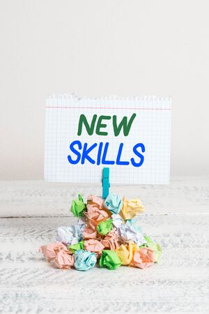 Text sign showing New Skills. Business photo text Recently Acquired Learned Abilities Knowledge Competences Reminder pile colored crumpled paper clothespin reminder white wooden space