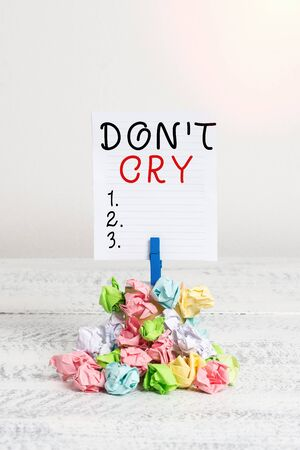 Conceptual hand writing showing Don T Cry. Concept meaning Shed tears typically as an expression of distress pain or sorrow Reminder pile colored crumpled paper clothespin wooden space