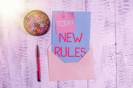 Conceptual hand writing showing New Rules. Concept meaning recently one of a set of explicit or understood regulations Envelope letter sticky note ballpoint clips on wooden background