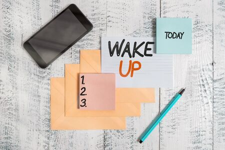 Word writing text Wake Up. Business photo showcasing an instance of a demonstrating waking up or being woken up Rise up Envelopes marker ruled paper smartphone sheet note pads wooden background Reklamní fotografie