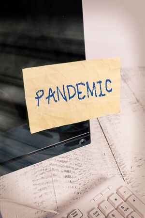 Writing note showing Pandemic. Business concept for occurring over a wide area affecting high proportion of population Notation paper computer monitor screen near white keyboard Stock fotó