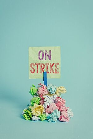 Text sign showing On Strike. Business photo text refuse to continue working because of an argument with an employer Reminder pile colored crumpled paper clothespin reminder blue background