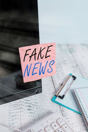 Text sign showing Fake News. Business photo text false information publish under the guise of being authentic news Note paper taped to black computer screen near keyboard and stationary Stock Photo