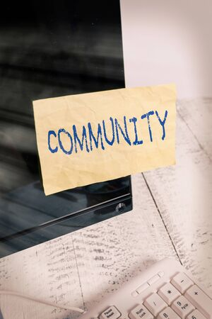 Writing note showing Community. Business concept for group of showing with a common characteristics living together Notation paper computer monitor screen near white keyboard