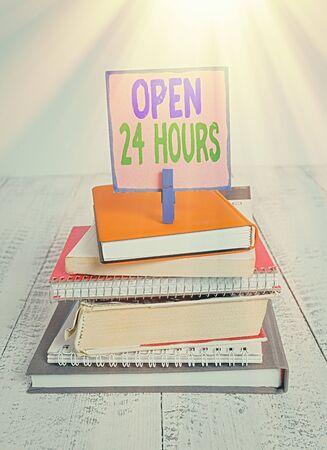 Writing note showing Open 24 Hours. Business concept for available all day and all night without closing or stopping pile stacked books notebook pin color reminder white wooden Archivio Fotografico