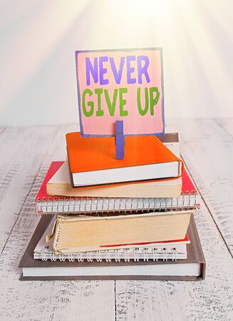 Writing note showing Never Give Up. Business concept for be persistent to keep on trying to improve the condition pile stacked books notebook pin color reminder white wooden