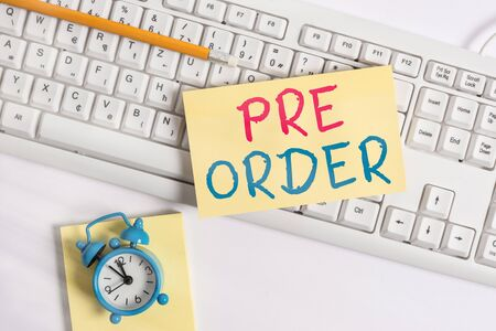 Writing note showing Pre Order. Business concept for an order for a product placed before it is available for purchase Flat lay above empty note paper on the pc keyboard pencils and clock