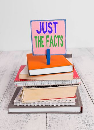 Writing note showing Just The Facts. Business concept for to have the correct information about the exact details pile stacked books notebook pin color reminder white wooden Zdjęcie Seryjne
