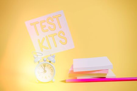 Text sign showing Test Kits. Business photo text tools used to detect the presence of something in the body Alarm clock blank pencil sticky note stacked notepads colored background