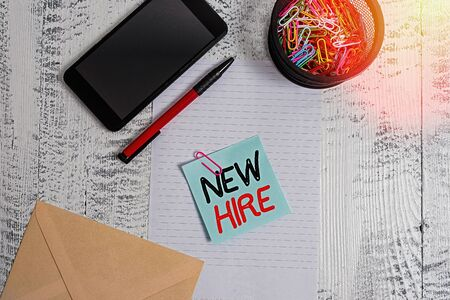 Handwriting text New Hire. Conceptual photo someone who has not previously been employed by the organization Smartphone paper sheet clips holder pen envelope note wooden background
