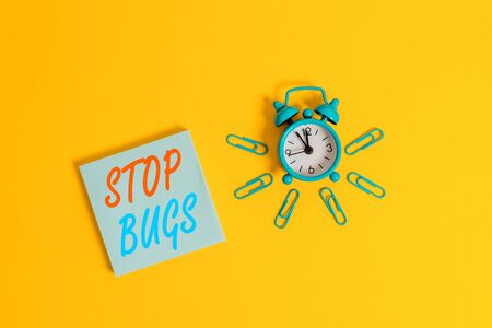 Conceptual hand writing showing Stop Bugs. Concept meaning Get rid an insect or similar small creature that sucks blood Metal vintage alarm clock clips notepad colored background