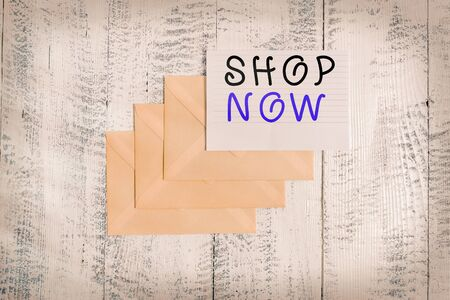 Handwriting text Shop Now. Conceptual photo the action or activity of purchasing goods from stores or online Three envelopes around ruled paper sheet old wooden vintage background
