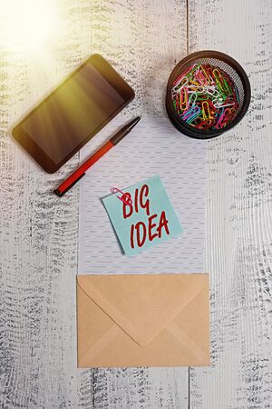 Word writing text Big Idea. Business photo showcasing Having great creative innovation solution or way of thinking Smartphone paper sheet clips holder pen envelope note wooden background