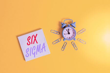 Conceptual hand writing showing Six Sigma. Concept meaning set of management techniques intended to improve business process Metal vintage alarm clock clips notepad colored background