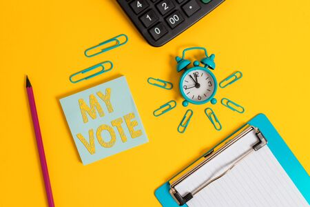 Writing note showing My Vote. Business concept for the act of showing your choice or opinion in an election or meeting Alarm clock clipboard pencil calculator notepad colored background