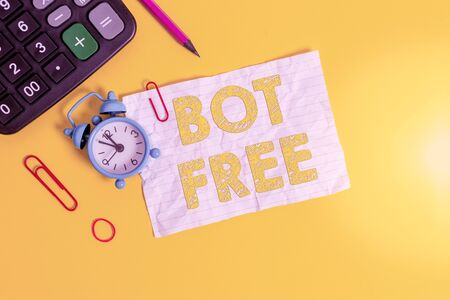 Handwriting text writing Bot Free. Conceptual photo a computer program that works automatically Internet robots Alarm clock clips note rubber band calculator pencil colored background