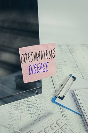 Text sign showing Coronavirus Disease. Business photo text defined as illness caused by a novel virus SARSCoV2 Note paper taped to black computer screen near keyboard and stationary