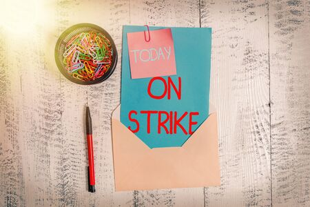 Conceptual hand writing showing On Strike. Concept meaning refuse to continue working because of an argument with an employer Envelope letter sticky note ballpoint clips on wooden background 版權商用圖片