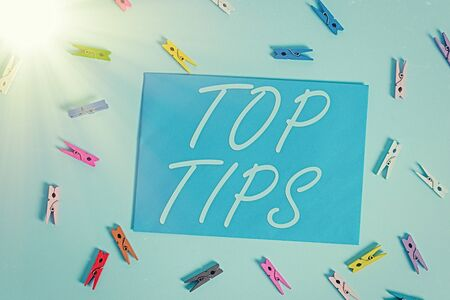 Text sign showing Top Tips. Business photo showcasing a small but particularly useful piece of practical advice Colored clothespin rectangle shaped reminder paper light blue background
