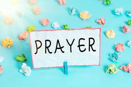 Conceptual hand writing showing Prayer. Concept meaning solemn request for help or expression of thanks addressed to God Colored crumpled papers empty reminder blue floor clothespin