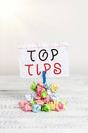 Handwriting text writing Top Tips. Conceptual photo a small but particularly useful piece of practical advice Reminder pile colored crumpled paper clothespin reminder white wooden space Foto de archivo