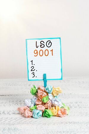 Handwriting text Iso 9001. Conceptual photo designed help organizations to ensure meet the needs of customers Reminder pile colored crumpled paper clothespin reminder white wooden space