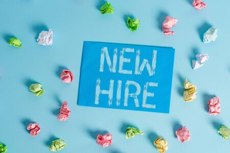 Conceptual hand writing showing New Hire. Concept meaning someone who has not previously been employed by the organization Colored clothespin rectangle shaped paper blue background