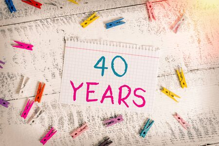 Word writing text 40 Years. Business photo showcasing Remembering or honoring special day for being 40 years in existence Colored clothespin rectangle square shaped paper white wood background