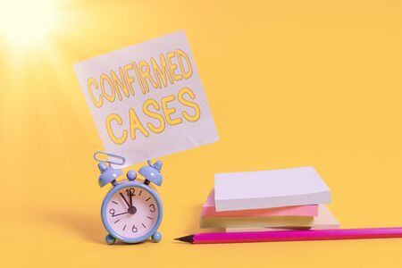 Text sign showing Confirmed Cases. Business photo text set of circumstances or conditions requiring action Alarm clock blank pencil sticky note stacked notepads colored background
