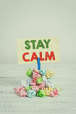 Word writing text Stay Calm. Business photo showcasing Maintain in a state of motion smoothly even under pressure Reminder pile colored crumpled paper clothespin reminder white wooden space