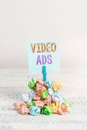 Text sign showing Video Ads. Business photo showcasing Engage audience in the form of video content advertising Reminder pile colored crumpled paper clothespin reminder white wooden space