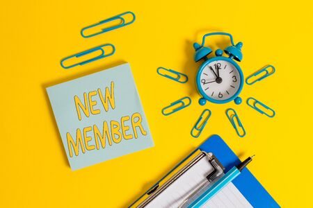 Handwriting text writing New Member. Conceptual photo recruiting employee to company or team Birth of fresh child Metal alarm clock clipboard clips ballpoint notepad colored background