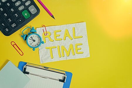 Writing note showing Real Time. Business concept for the actual time during which a processes or events occurs Alarm clock crushed note calculator pencil clipboard color background