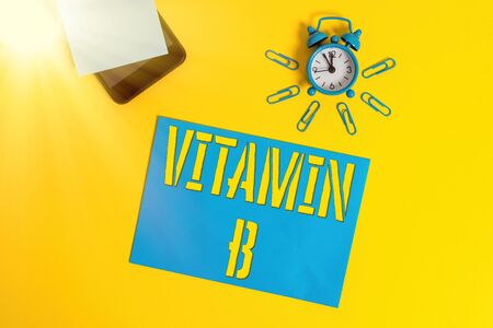 Handwriting text Vitamin B. Conceptual photo Nutrient that helps keep the body nerve and blood cells healthy Smartphone metal alarm clock clips paper sheet notepad colored background Standard-Bild