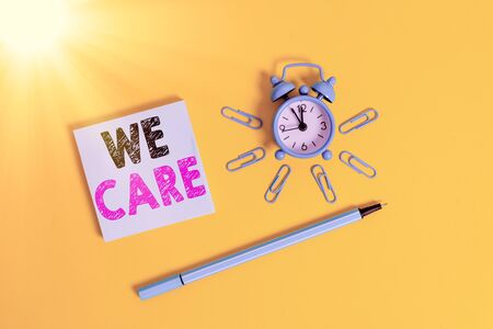 Writing note showing We Care. Business concept for Cherishing someones life Giving care and providing their needs Metal alarm clock wakeup clips ballpoint notepad colored background Zdjęcie Seryjne