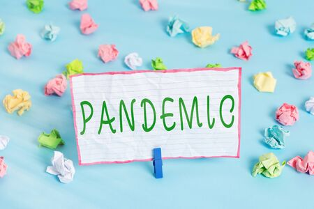 Conceptual hand writing showing Pandemic. Concept meaning occurring over a wide area affecting high proportion of population Colored crumpled papers empty reminder blue floor clothespin
