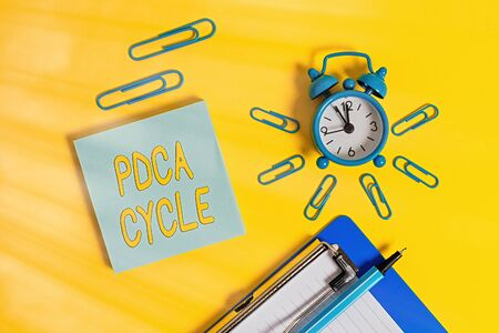 Handwriting text writing Pdca Cycle. Conceptual photo use to control and continue improve the processes and products Metal alarm clock clipboard clips ballpoint notepad colored background