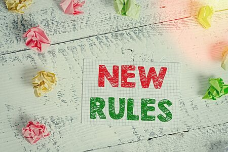 Text sign showing New Rules. Business photo text recently one of a set of explicit or understood regulations Crumpled colored rectangle square shaped paper reminder white wood desk