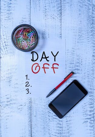 Text sign showing Day Off. Business photo text when you do not go to work even though it is usually a working day Smartphone paper sheet clips holder ballpoint wooden vintage background