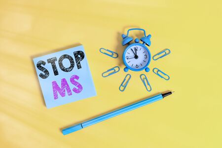 Writing note showing Stop Ms. Business concept for treat the condition that can affect the brain and spinal cord Metal alarm clock wakeup clips ballpoint notepad colored background